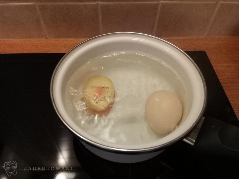 Jajko ugotowane na twardo w garnku wody.